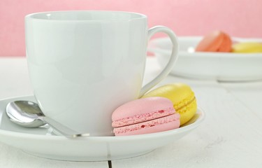 Macaroon biscuits with cup and plate on a white wooden table