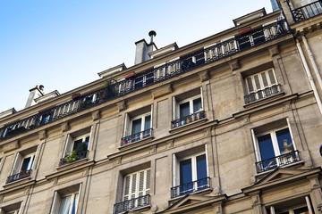 Верхние этажи жилого дома в Париже на фоне голубого неба.