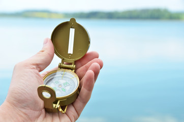 Compass in the hand against lake