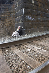 Homeless Man Living Under Railroad Bridge