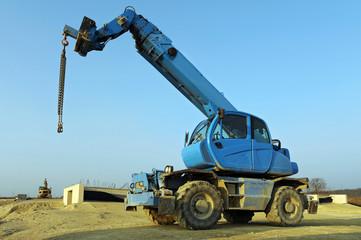 Blauer Kran mit Rädern auf Baustelle