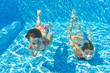 Happy girls swim underwater in pool and having fun