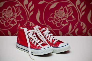 красная спортивная обувь на бордовом фоне