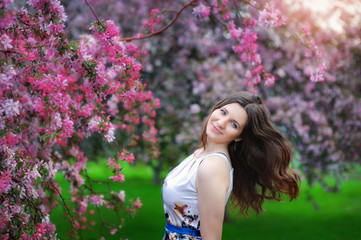 Beautiful young girl in spring flowers garden lifestyle portrait