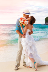 Wedding. Bbride and groom kissing on the tropical coast at sunse