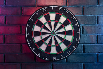 Dart board on a brick wall with dramatic lighting