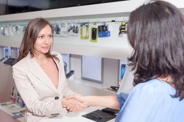 Handshake zwischen Kunde und Verkäuferin