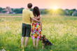 Young couple hugging in the field and looking at the village at