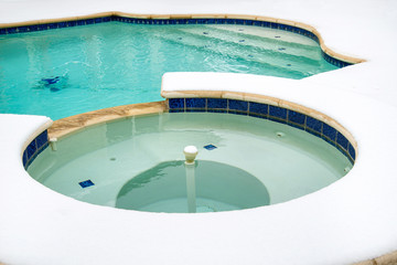Outdoor hot tub or spa by swimming pool in snow