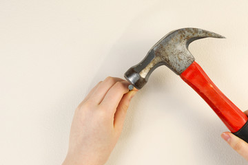 Hands holding hammer and nail against home interior wall