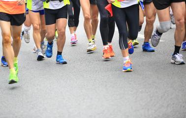 Unidentified marathon athletes legs running on street