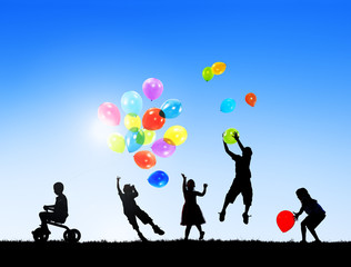Silhouettes of Children Playing Balloons Outdoors