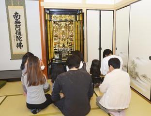 仏壇に手を合わせる家族