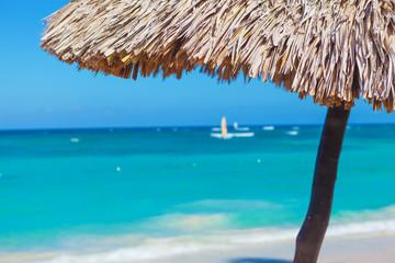straw umbrella closeup on a beautiful tropical beach