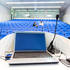 Laptop on the rostrum in conference hall.