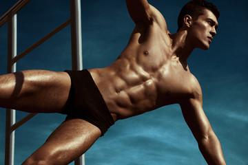 Muscular athletic sportsman in training. Winner.