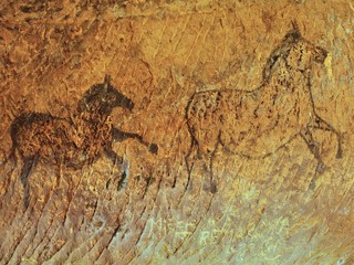 Abstract children art in sandstone cave. Paint of horses on wall