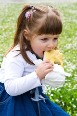 little beautiful girl eating a olives bun