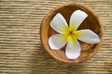 frangipani in water wooden bowl on Brown straw mat