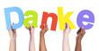 Multiethnic Group of Hands Holding Word Danke