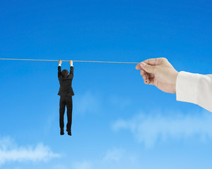 Businessman holding rope in blue sky