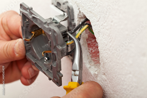 Electrician hands installing wires into electrical outlet - 64565439