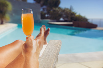 Young lady with orange juice sunbathing at the poolside