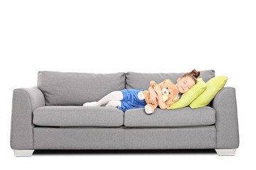Girl hugging a teddy bear and sleeping on couch