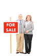 Mature husband and wife standing by for sale sign