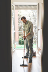 handsome stylish man using hoover