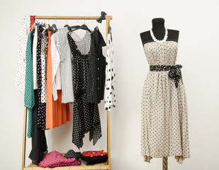 Dressing closet with polka dots clothes and dress on mannequin.