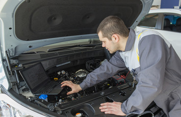 professional car mechanic in auto repair service with laptop
