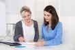 Zwei Frauen sitzen gemeinsam im Büro an einem Tisch