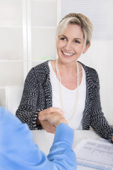 Attraktive Geschäftsfrau - Handschlag bei Vertragsabschluss
