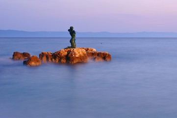 Statue of the mermaid in Podgora in evening, Croatia