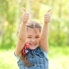 Portrait of happy girl showing thumbs up gesture