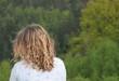 Mädchen mit lockigem Haar vor Naturlandschaft