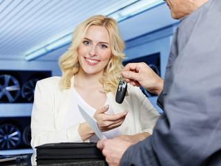 Female customer gets her car key after service