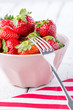 Strawberries in a pink bowl.