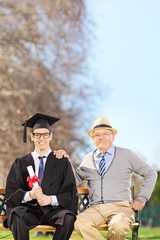 College graduate posing with his father in park