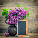 bouquet of lilac flowers. blackboard for your text - 64574216