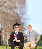 Male graduate posing with his proud father in park