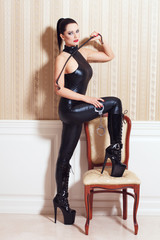 Sexy woman in latex catsuit at vintage wall