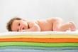 newborn baby girl  lying on colourful towels