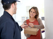 Woman sigining electronic receipt of delivered package - 64575663