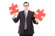 Young businessman holding two pieces of puzzle