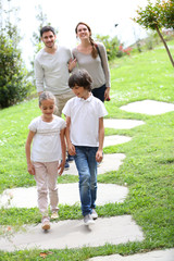 Happy family of four walking towards home