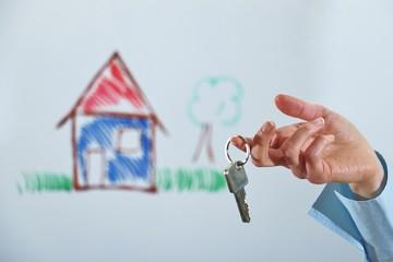 Frauen hand hält schlüssel zum eigenheim, symbol