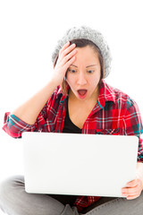 Young woman looking shock while using laptop