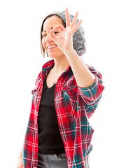 Young woman looking through fingers, making 'ok' sign